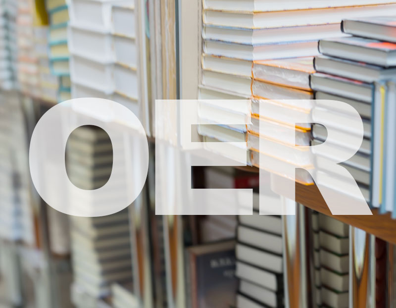 """Stack of books in background of letters """"OER"""""""