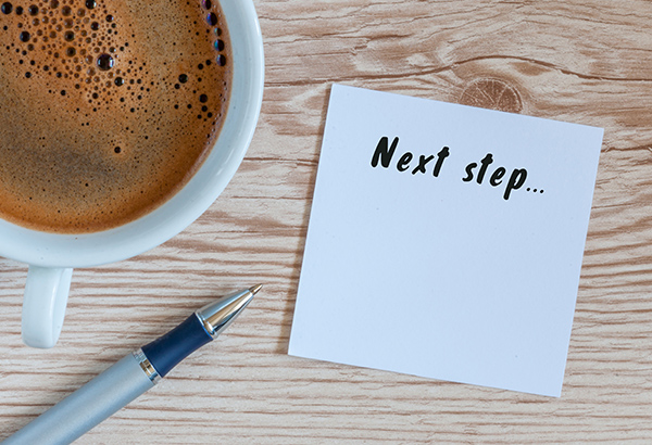 """Coffee and pen sit on table with a notepad that says, """"Next step..."""""""
