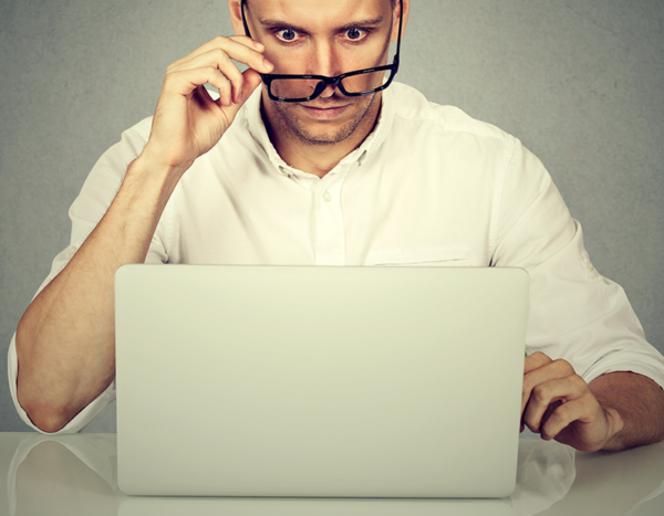 Man looks at computer with eyes raised and holds glasses on the tip of his nose