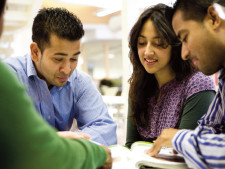 Students of different ethnicities sit down at table and collaborate