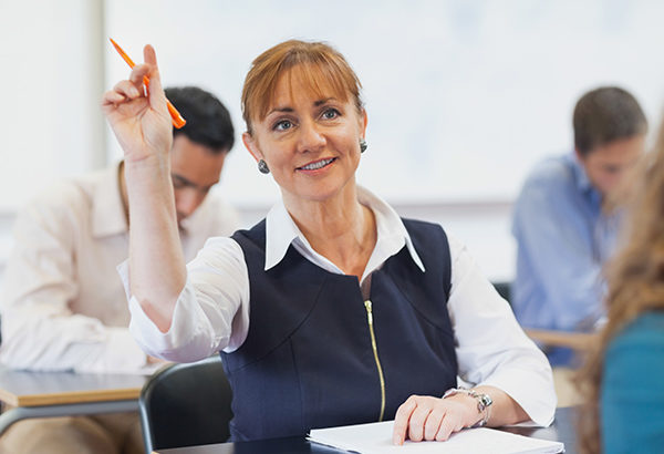 Middle-aged woman raises hand in class with questions
