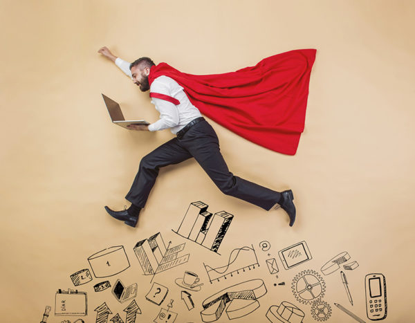 Man in superhero cape holds computer while jumping over doodles of school related images