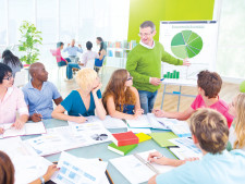 Colorful papers line meeting room table with person giving presentation to others