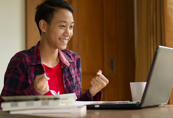 Student looks at computer with fists of success while smiling