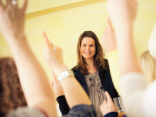 Multiple hands are raised while teacher smiles in front of classroom