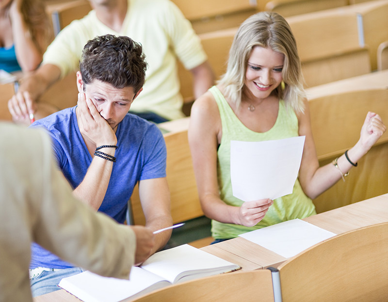 Student looks down at book with hand on face looking unhappy