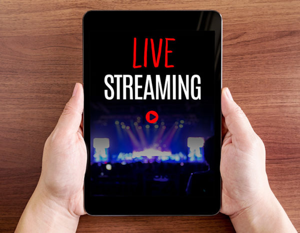 """Person holds tablet with the words """"live streaming"""" on screen and play button"""