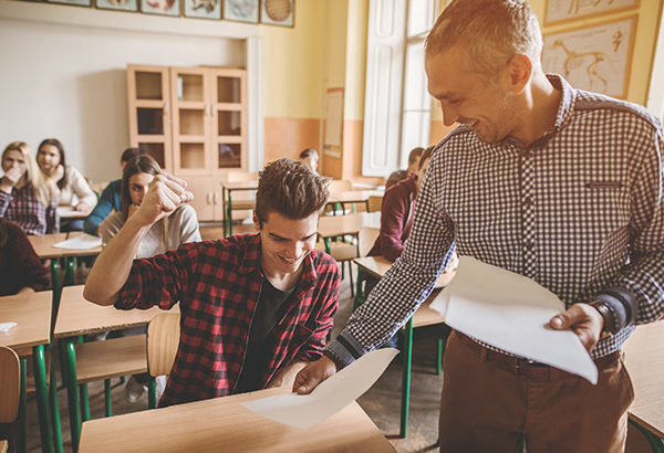 Professor hands back exam to student and student raises hand in air in success
