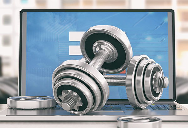 Weight-lifting weights are set on top of computer keyboard and computer screen