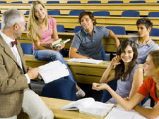 Group of students sit in large lecture hall discussing with teacher