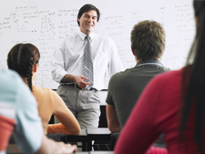 Instructor teaches in front of students with wipe-off board in back of him