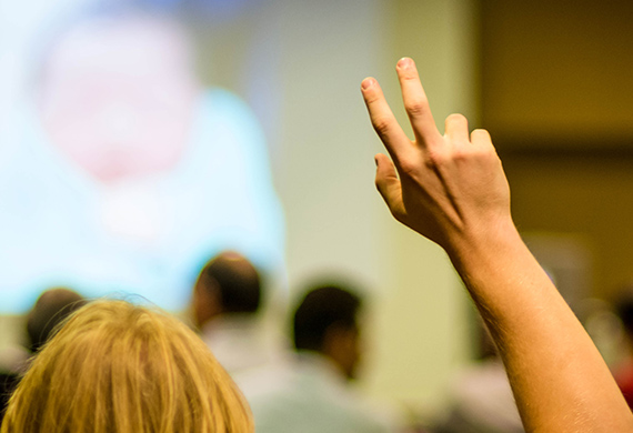 Person raises hand during class with projector screen in background