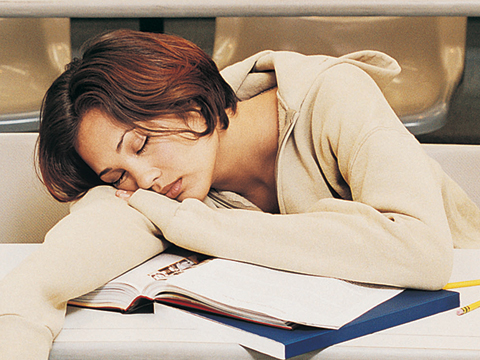 Student falls asleep at desk on top of pile of books and notebooks