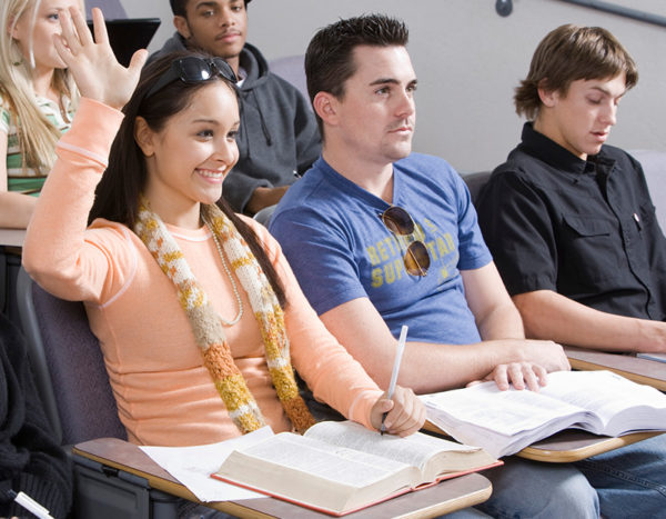 Students sit in desks and girl raises her hand