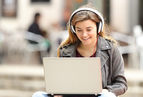 Person smiles at computer with headphones