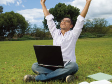 Person sits outside with computer on lap and stretches arms into the air with excitement
