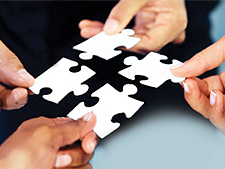People hold puzzle pieces and connect them together