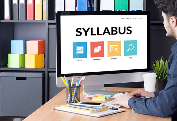 """Person looks at computer screen in office with the word, """"Syllabus"""" on the computer screen"""