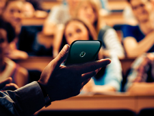 Instructor holds up cellphone to students in lecture