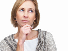 Woman ponders while putting hand on chin