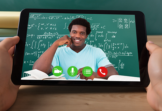 Person in front of chalkboard is featured on tablet on Zoom call