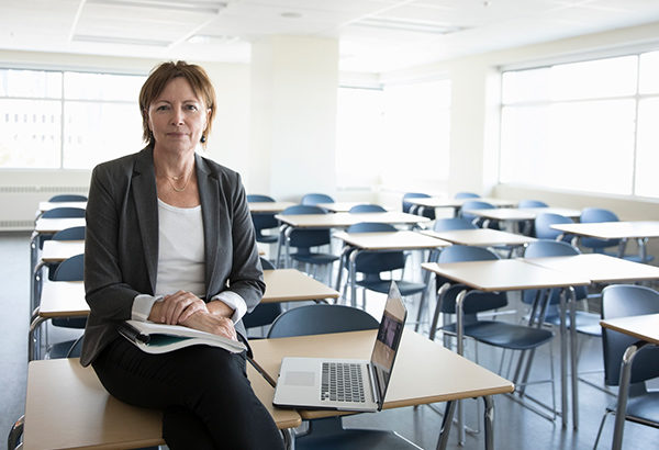 Instructor sits on desk with computer with empty classroom of desks