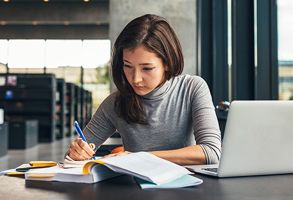Woman looks at notes and writes in notebook with computer screen opened