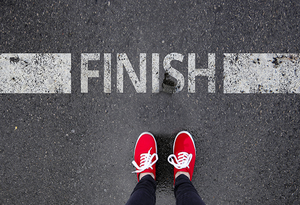 Tennis shoes stand in front of finish line