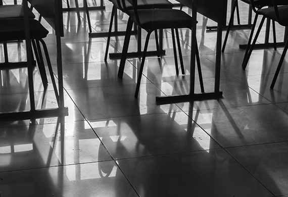 Empty classroom and empty chairs cast shadows