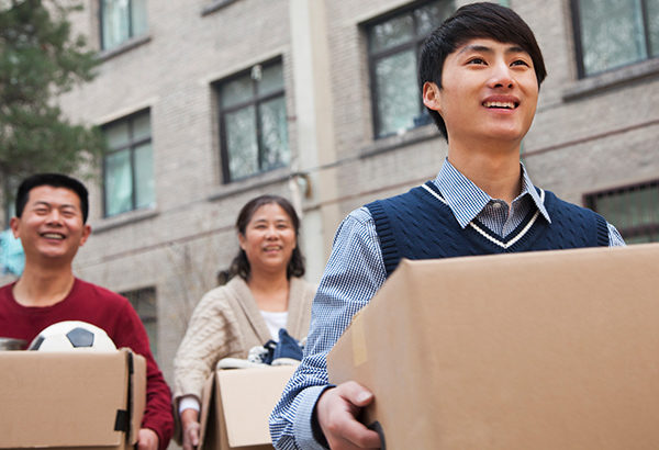 Upcoming students walk into dorm with boxes