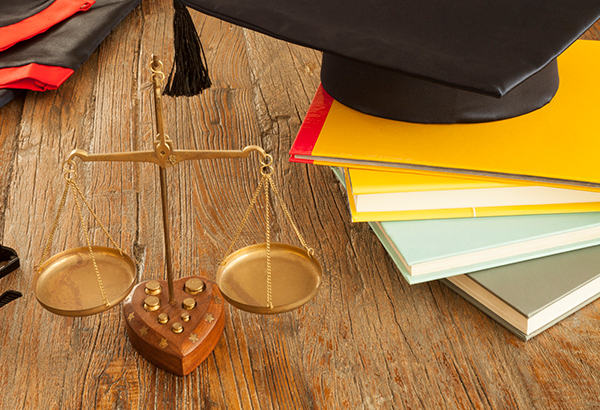 Graduation cap, a balance of justice and books sit on table