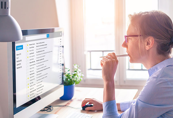Person looks at computer online with pen in mouth