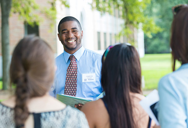 Student leader greets oncoming students to campus