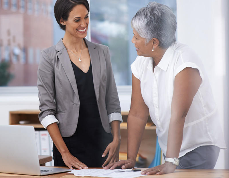 Two people talk with one another while leaning on desk at school