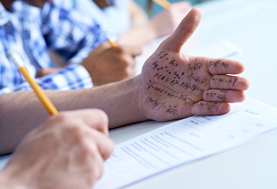 Student takes test and looks at hand with cheat notes written on hand