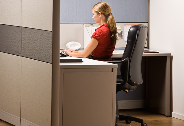 Person sits in office chair in cubicle