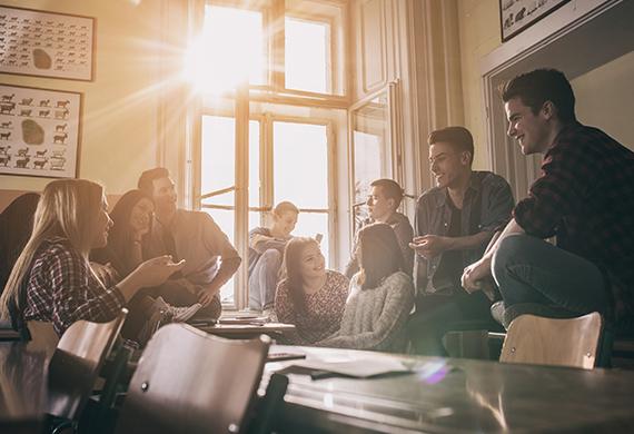 Students sit and stand over table while talking and sun shines through window