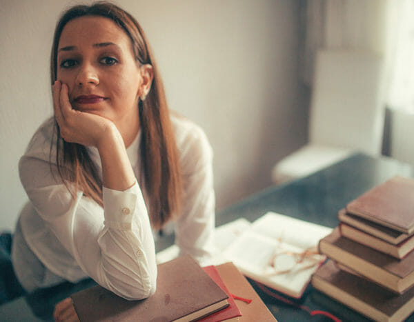 Person rests head in hand with stack of books in front of her