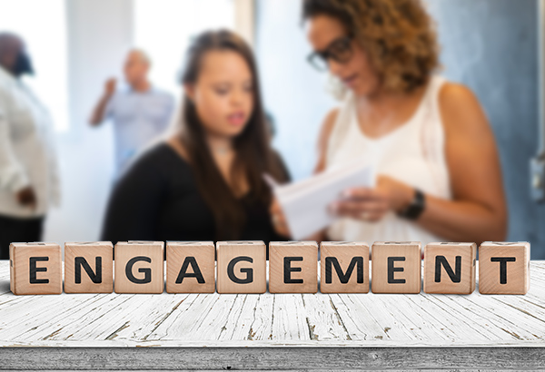 "People in background are blurred with letter blocks in the forefront spelling, ""engagement"""