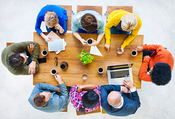 Employees collaborate around table with coffee discussing work