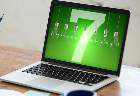 Computer displays green background with the number 7 and lightbulbs hanging with one lit