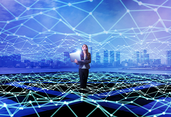 Business woman holds computer with lines of electricity surrounding her and city sky view in the background
