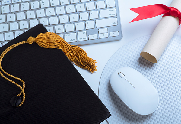 Graduation cap, computer keyboard, diploma and computer mouse lay on table