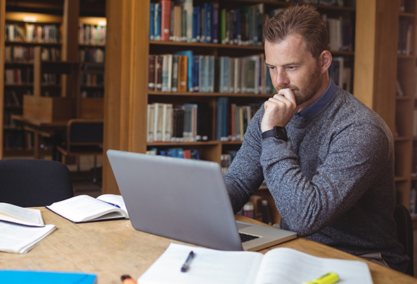 Man sits at desk while looking at computer screen with library books in background