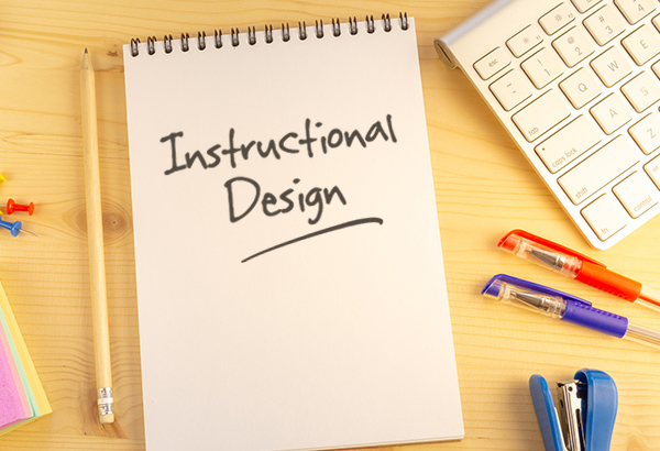 "Notebook has the words ""Instructional Design"" written on it with colored pens and pencils surrounding it"