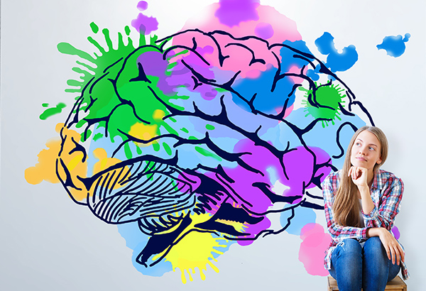 Girl sits on stool with image of brain painted behind her on wall with paint splatters