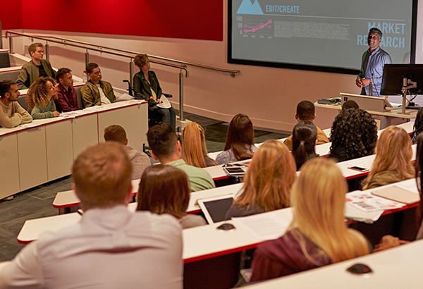 Large lecture hall filled with students look at project in front with instructor