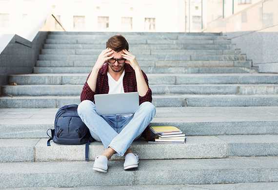 Student sits on stairs with head in hands looking at laptop