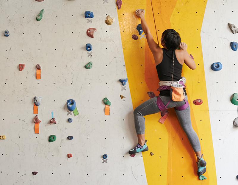 Woman climbs up rock climbing wall with hoist