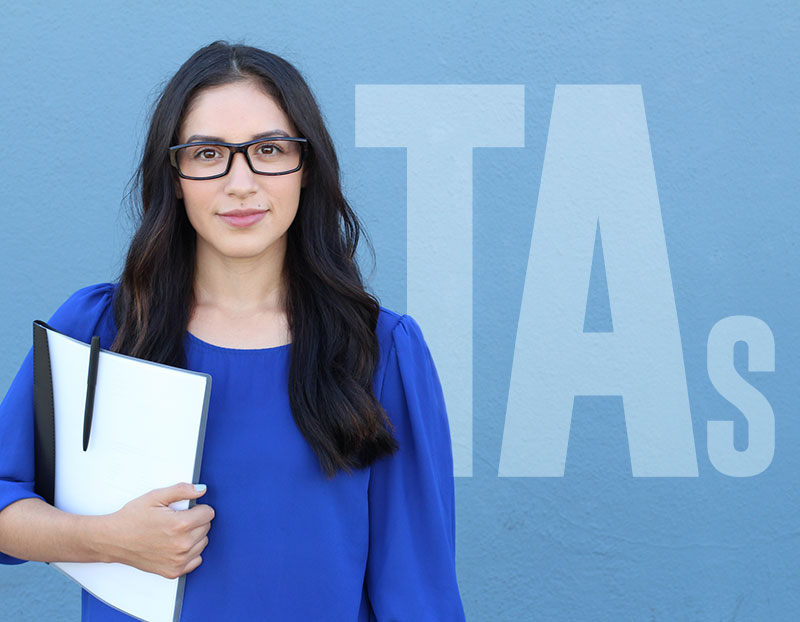 """Woman with papers and pen stands in front of sign that says, """"TAs"""""""